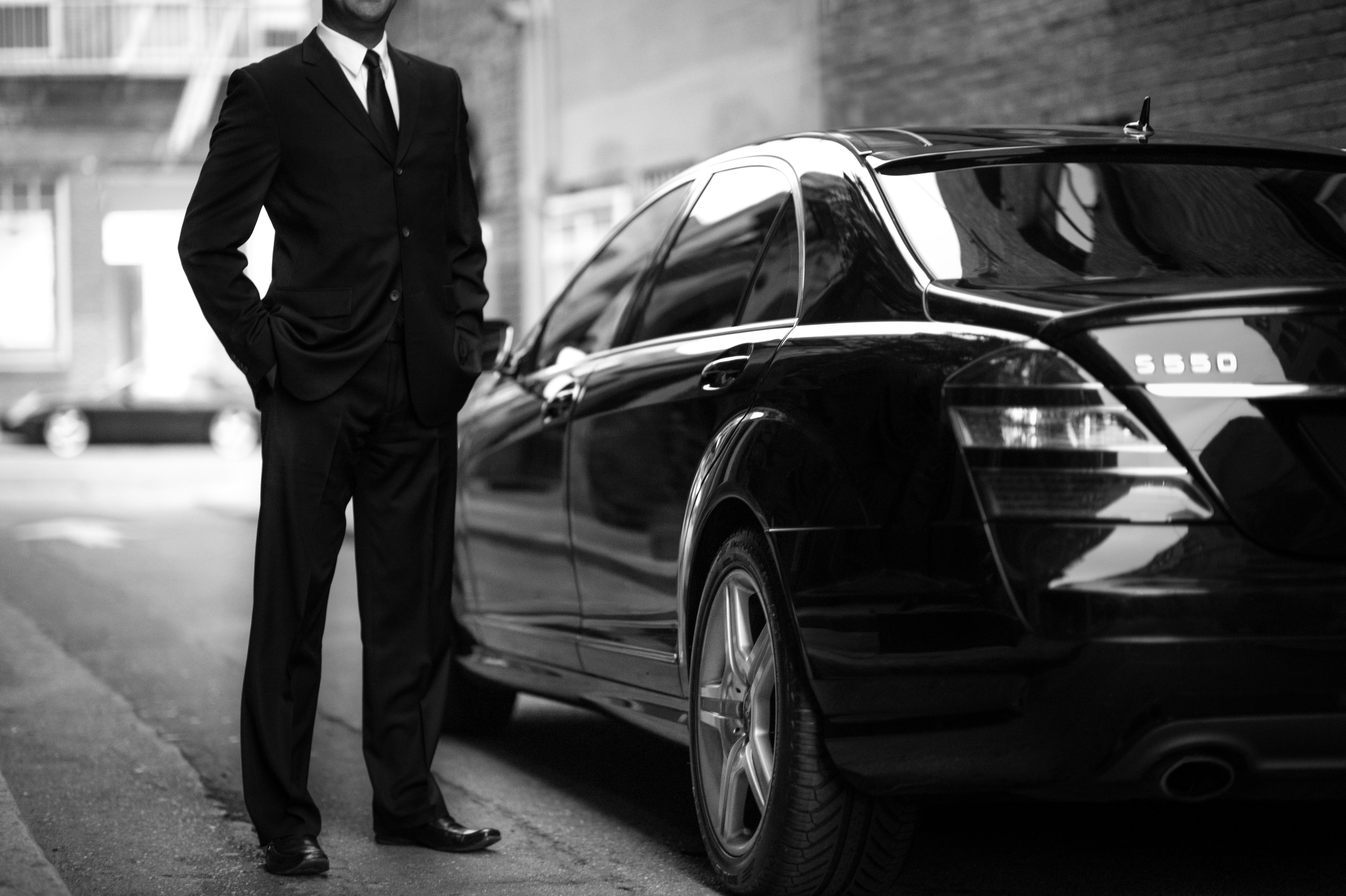 Uber sjåfør ved siden av sin bil.